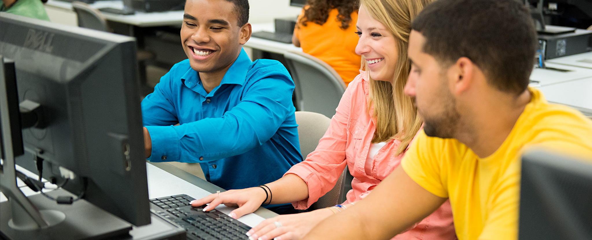 Students smile as they work together at a computer.